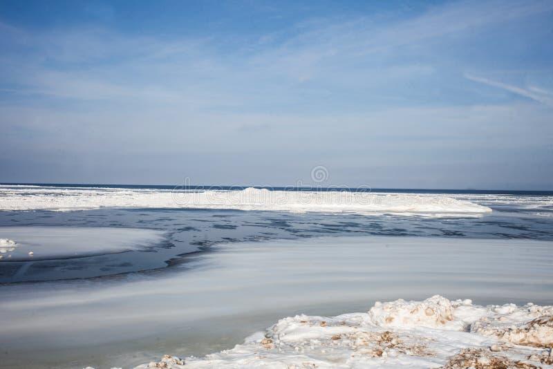 Lago e paesaggio congelati di inverno del ghiaccio della costa Turismo e pesca sul ghiaccio estremi immagine stock libera da diritti
