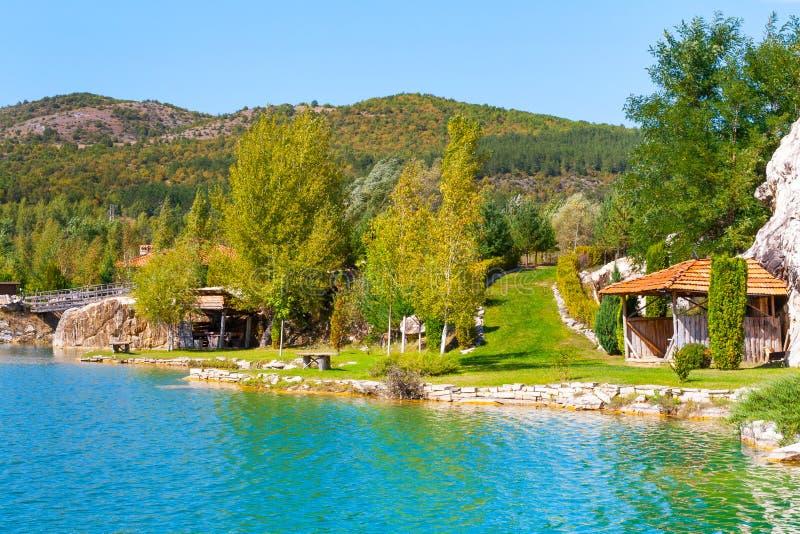 Lago e paesaggio verde degli alberi con le montagne immagine stock libera da diritti