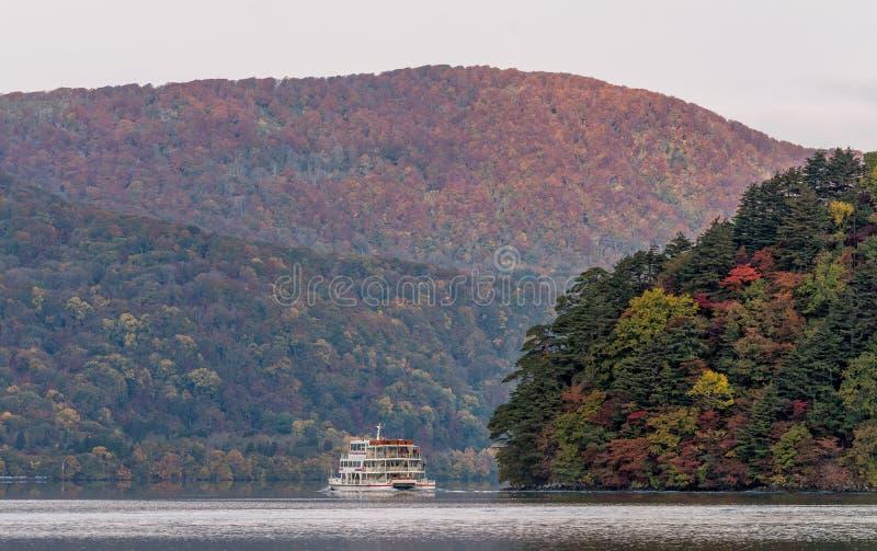 Lago e vista Towada que veem o barco cruzar durante a estação do outono imagem de stock