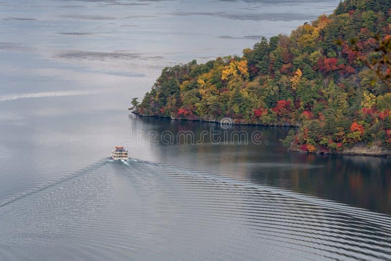 Lago e vista Towada que veem o barco cruzar durante a estação do outono fotos de stock royalty free