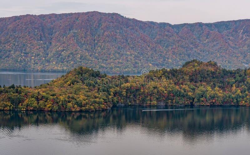 Lago e vista Towada que veem o barco cruzar durante a estação do outono imagens de stock
