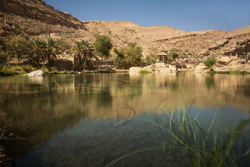 Lago ed oasi di stupore con le palme Wadi Bani Khalid nel deserto dell'Oman fotografia stock