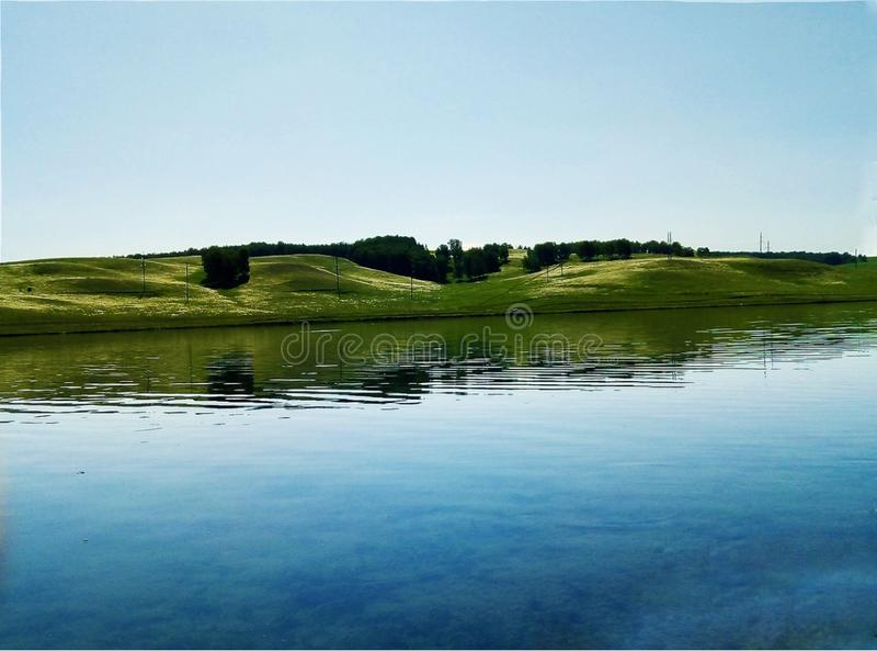 Lago em uma costa quieta em um céu raging de brilho e em um cenário bonito imagem de stock royalty free