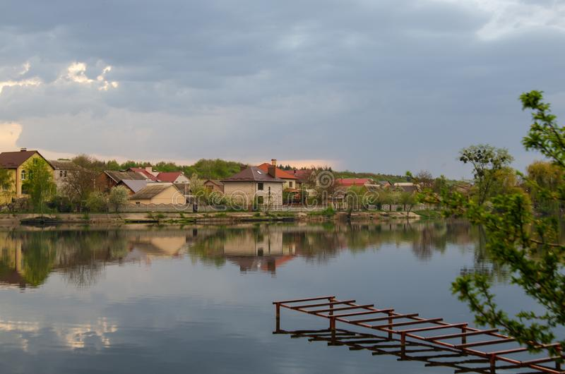 Lago em uma vila com uma reflexão do céu antes da chuva imagens de stock royalty free