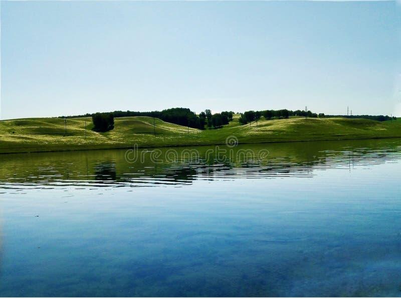 Lago en una orilla reservada en un cielo que rabia brillante y un paisaje hermoso imagen de archivo libre de regalías