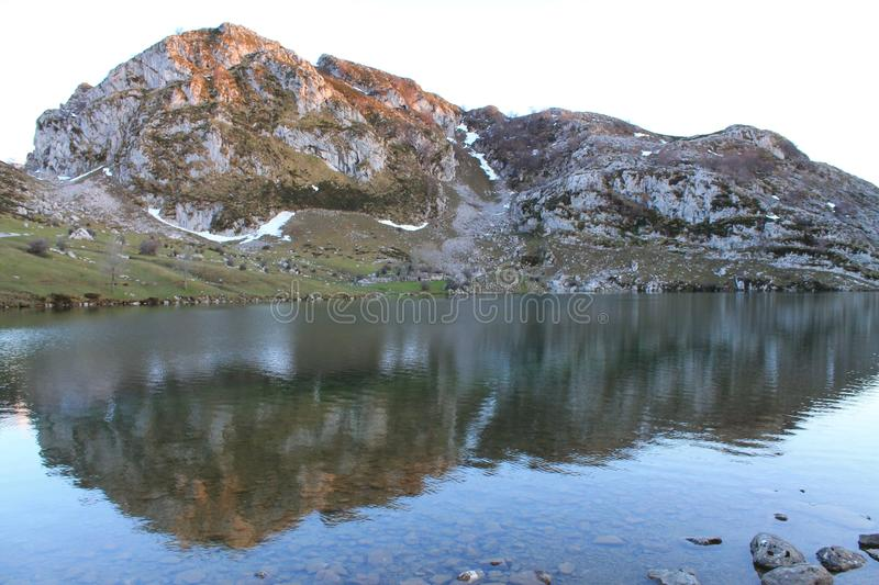 Lago Enol, Cangas de Onís, Spain. Picu L`Mosquital, 1,284 m, reflected in Lake Enol, at sunset. Lake Enol is a small highland lake in the Principality of royalty free stock photos