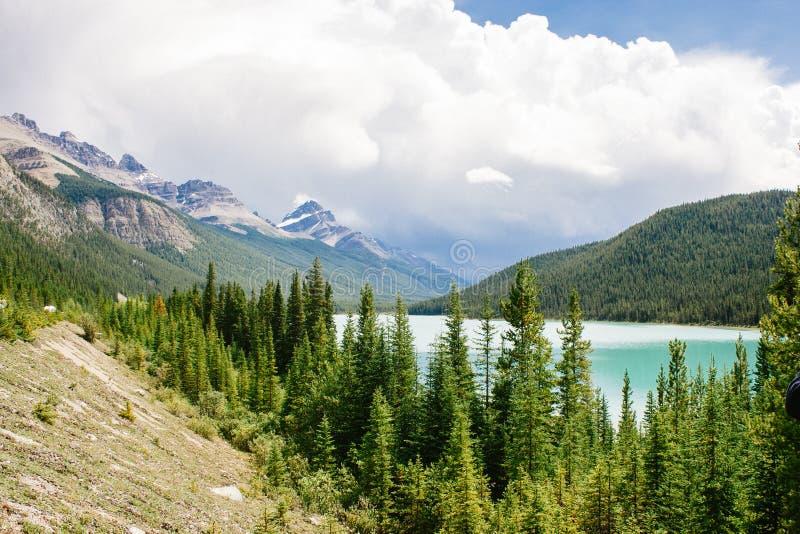 Lago entre los picos de montaña y el cielo nublado imagenes de archivo