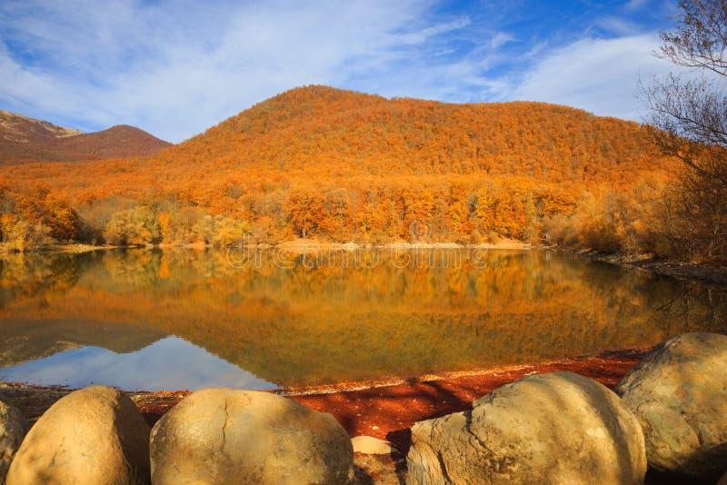 Lago escénico de la montaña con el bosque otoñal y piedras grandes a lo largo de t fotografía de archivo libre de regalías