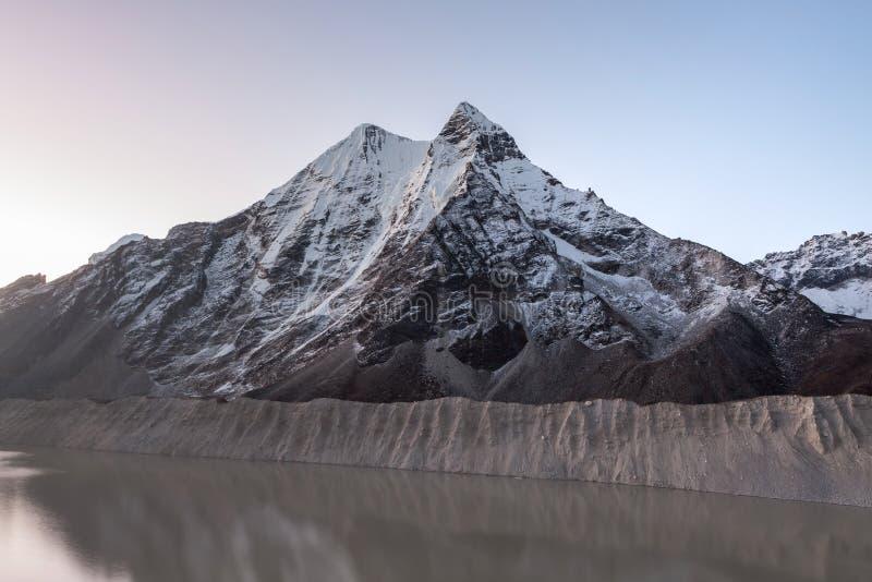 Lago gris de la moraine y pico de montaña nevoso en fotografía de archivo libre de regalías
