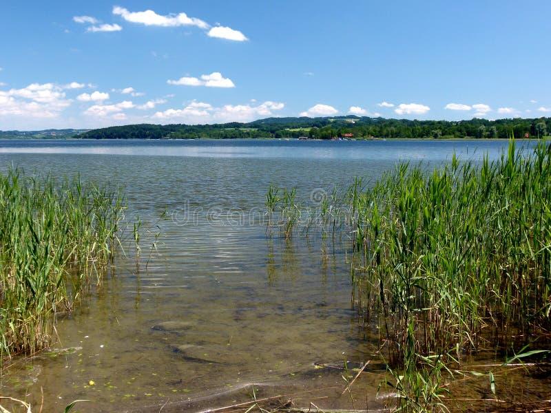 Lago hermoso con la correa de lámina en la orilla y tierra verde con contrario apacible de las colinas fotos de archivo