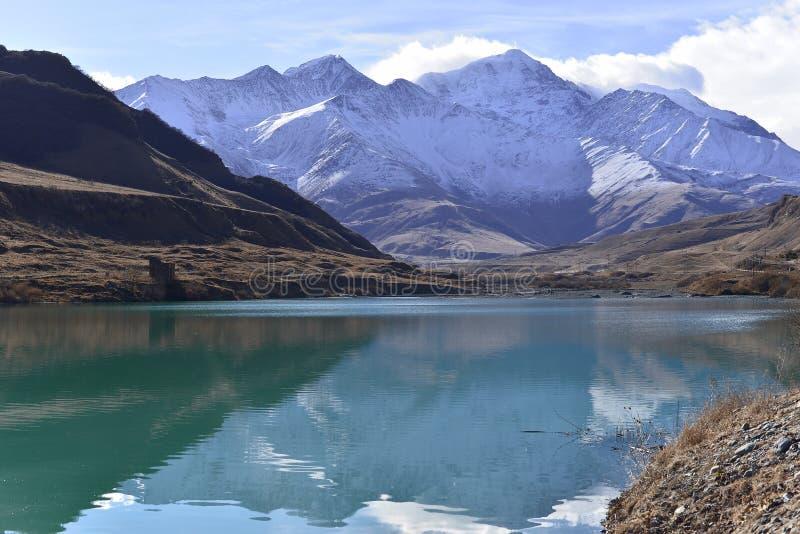 Lago hermoso de la turquesa en el medio de las montañas nevadas en un otoño soleado imagen de archivo libre de regalías