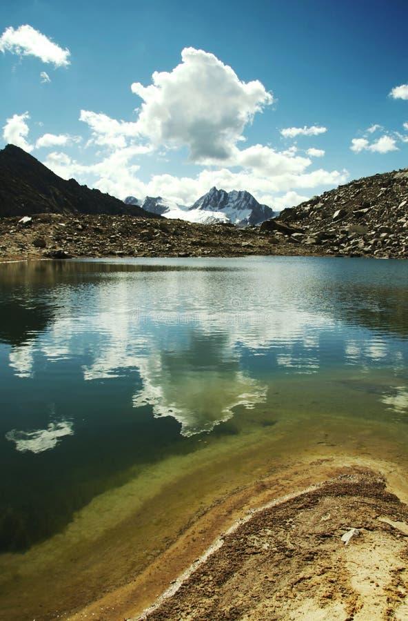 Lago hermoso en montaña y nubes imagen de archivo