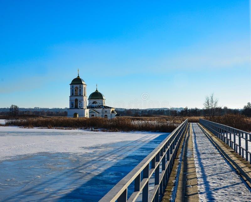 Lago innevato con un ponte del metallo verso la chiesa immagine stock