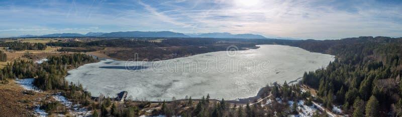 Lago Kirchsee, Baviera, con las montañas en fondo, en invierno de la primavera fotografía de archivo libre de regalías