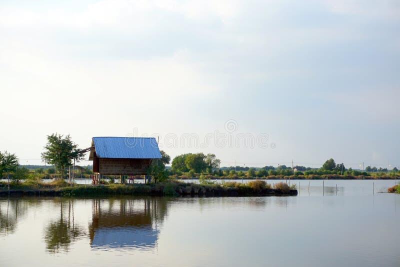 Lago landscape con el pueblo de la casa de la cabaña choza de la costa de la relajación fotografía de archivo libre de regalías
