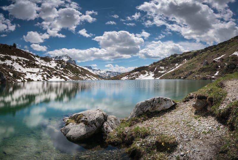 Lago lindo da montanha nos cumes com reflexões e restos da neve fotografia de stock
