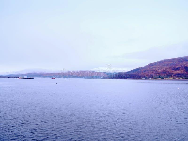 Lago liscio con le alte montagne del cono ed i picchi nevosi immagine stock libera da diritti