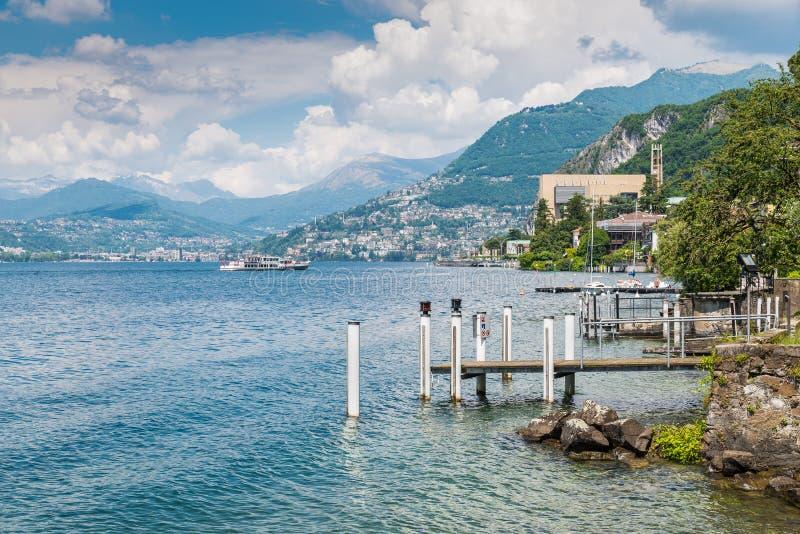 Lago Lugano Ideia do ` Italia de Campione d, famosa para seu casino visível no direito, com uma chegada do barco de turista fotos de stock