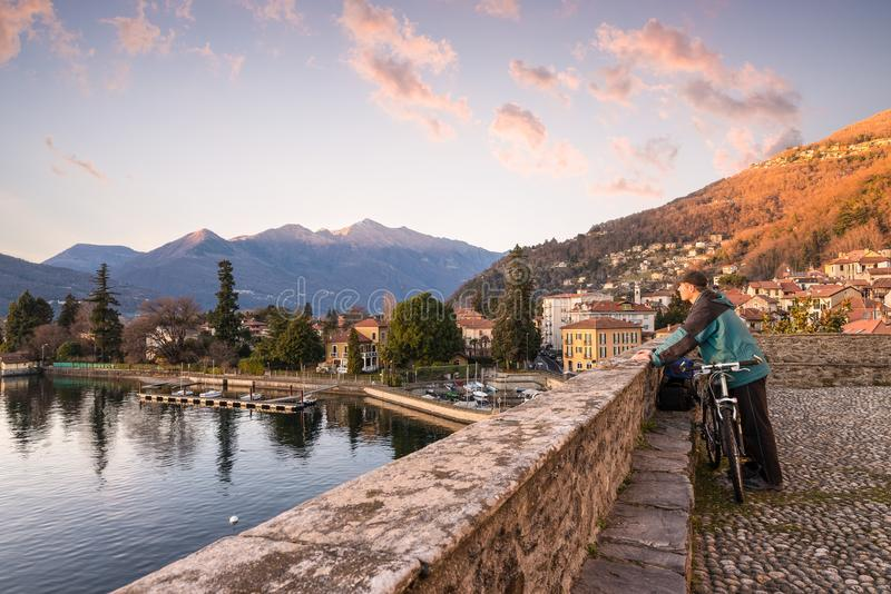 Lago Maggiore, Italia El turista con la bicicleta observa una puesta del sol hermosa foto de archivo libre de regalías
