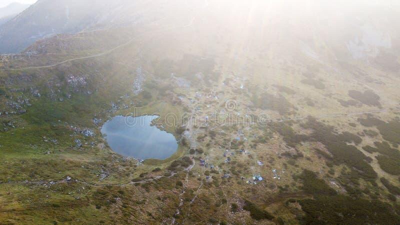Lago mountain con muchas tiendas de una opinión del s-ojo del ` del pájaro imagen de archivo
