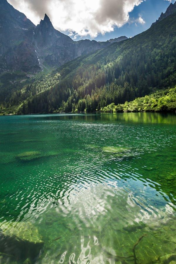 Lago mountain en el fondo de montañas rocosas fotos de archivo