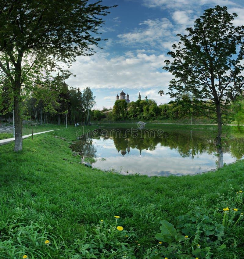 Lago nel parco con la chiesa nel giorno di estate fotografie stock