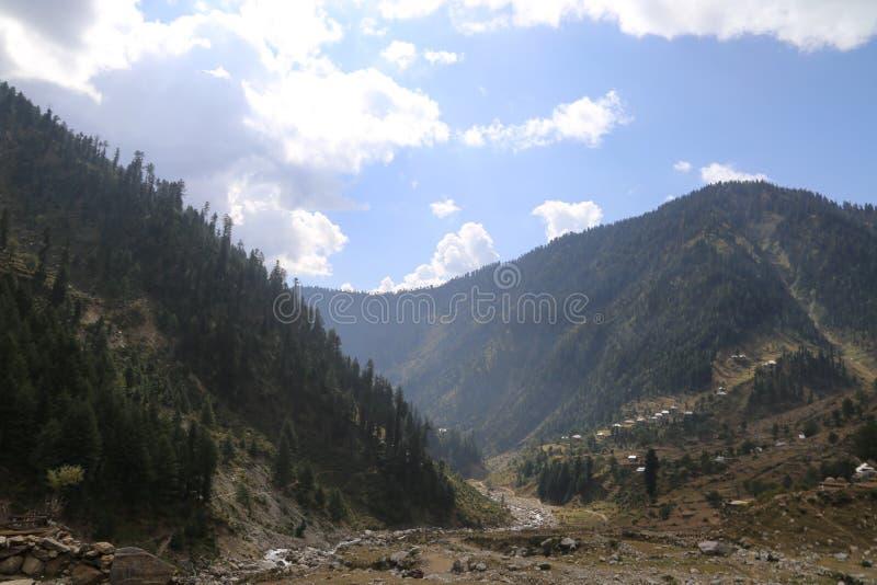 Lago pequeno que passa completamente entre as montanhas sob o céu azul fotografia de stock royalty free