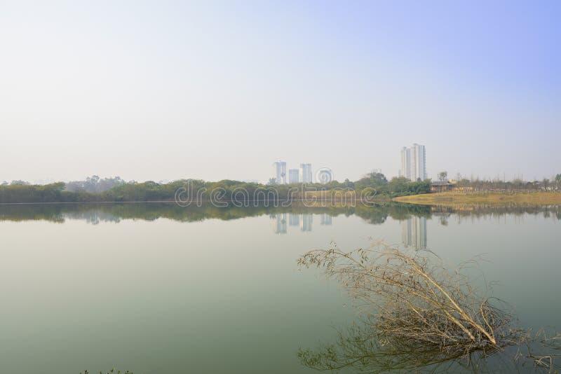 Lago perto da cidade moderna no meio-dia ensolarado do inverno imagens de stock