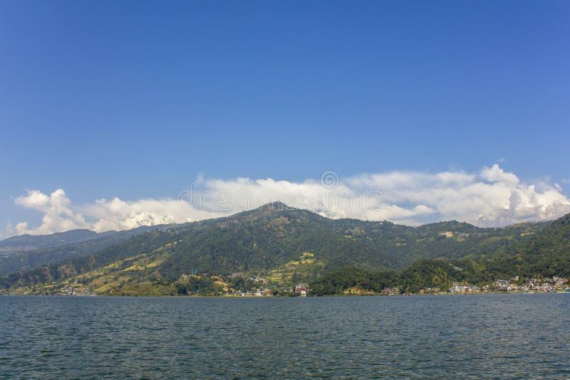Lago Phewa no fundo de um vale verde da montanha e na parte superior nevado da montagem Annapurna sob um céu azul, vista da água foto de stock