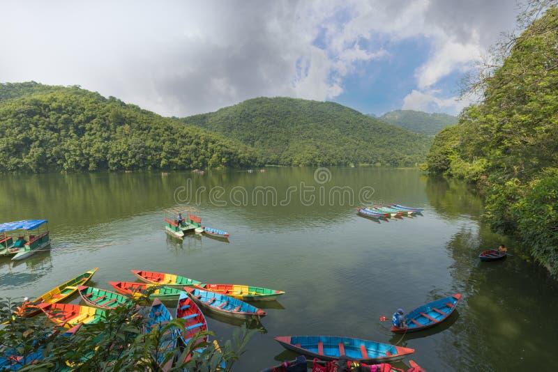 Lago Phewa un día nublado y barcos de madera del color en el lago imagen de archivo libre de regalías