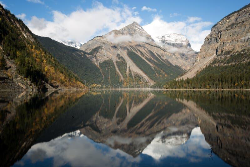 Lago reflexivo sob montanhas gigantes foto de stock