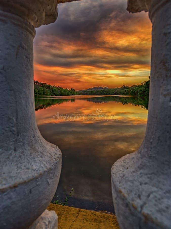 Lago rodeado por los árboles vistos entre los pilares en la puesta del sol fotografía de archivo