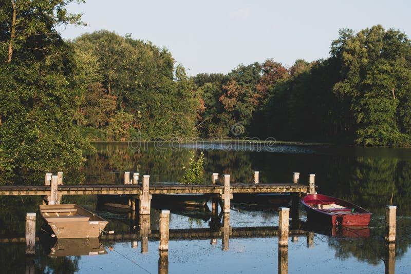 Lago romântico com molhe e barcos a remos na luz solar morna imagens de stock