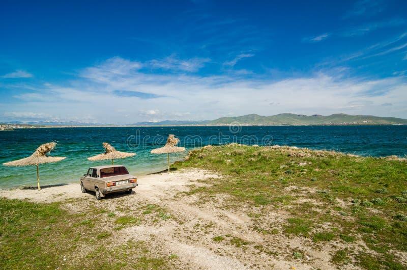 Lago Sevan, Armênia - 10 de maio de 2017 Carro retro de Ziguli estacionado na costa do lago claro em montanhas armênias, Armênia  fotos de stock royalty free