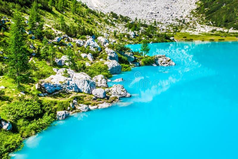 Lago Sorapis del turchese con i pini e le montagne della dolomia dentro fotografia stock libera da diritti