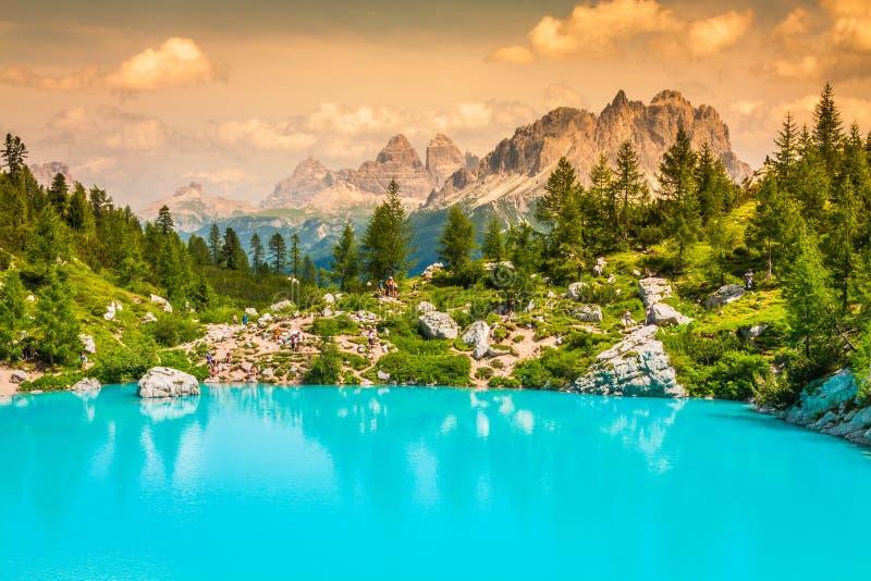 Lago Sorapis del turchese con i pini e le montagne della dolomia dentro immagine stock