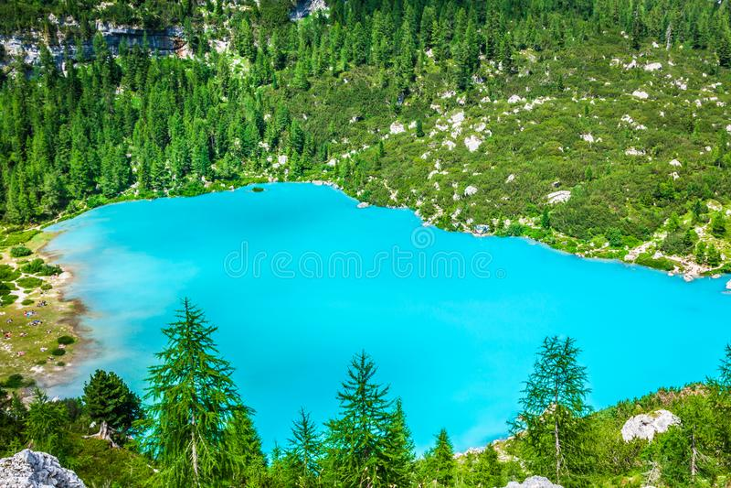 Lago Sorapis del turchese con i pini e le montagne della dolomia dentro immagine stock libera da diritti