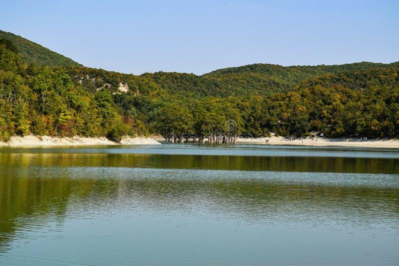 Lago Sukko, territorio di Krasnodar, Russia Ciclomotore nelle acque del lago Un lago fantastico tra le montagne immagini stock