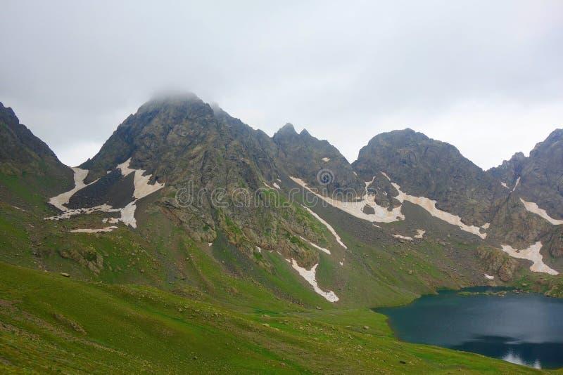 Lago Tobavarchkhili com uma passagem de montanha nevado em montanhas de Cáucaso em uma caminhada para pratear lagos em Geórgia fotos de stock royalty free
