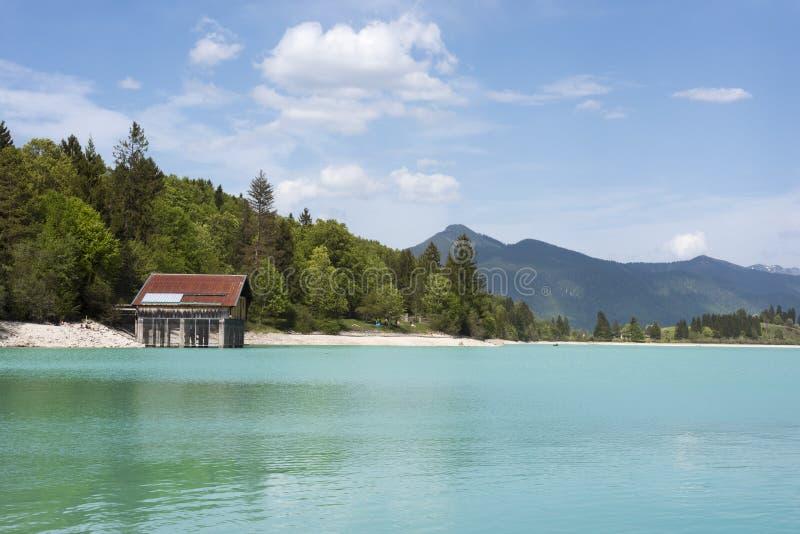 Lago Walchensee com estaleiro e cordilheira - lago alpino típico nos cumes bávaros com claro incrível e turquesa foto de stock