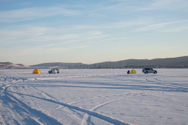 Lago winter com barracas e carros dos fishermens na perspectiva das montanhas foto de stock royalty free