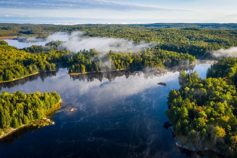 Lago y bosque brumosos de una opinión de alto ángulo foto de archivo libre de regalías