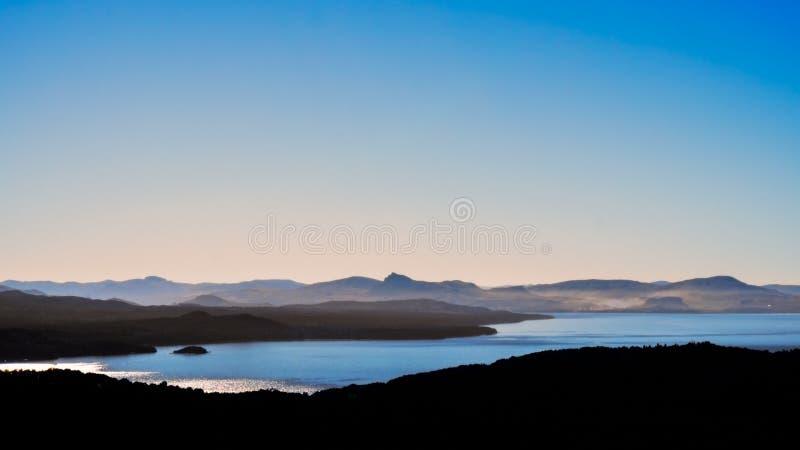 Lago y montaña Silhouttes en el crepúsculo imagen de archivo