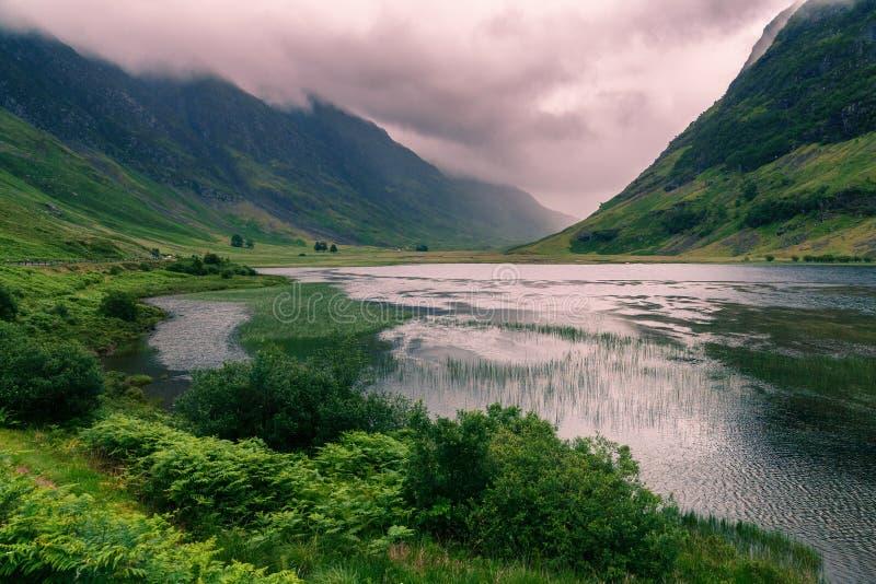 Lago y montañas con las nubes dramáticas, Escocia foto de archivo libre de regalías