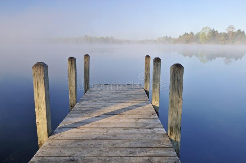 Lago y muelle brumosos fotos de archivo