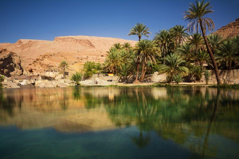 Lago y oasis con las palmeras Wadi Bani Khalid en el desierto omaní imagenes de archivo