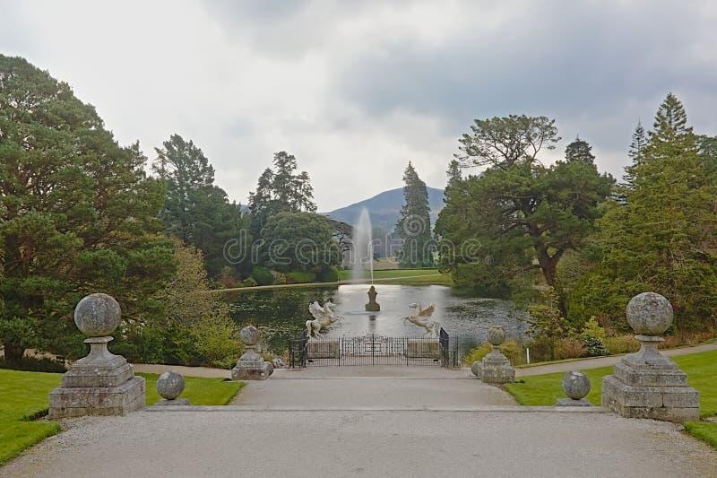 Lagoa com árvores e no jardim de Powerscourt e na grande montanha do naco de açúcar, Enneskery imagens de stock