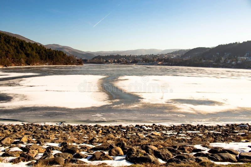 A lagoa congelada, pedras no primeiro plano está na neve, céu azul claro imagem de stock