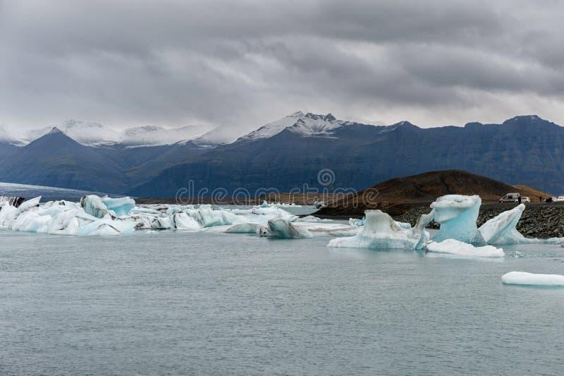 Lagoa da geleira de Jokulsarlon em Islândia Céu nebuloso, montanha no fundo fotografia de stock