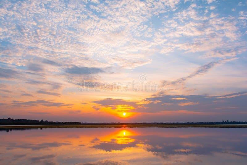Lagoa da reflexão do por do sol por do sol bonito atrás das nuvens e do céu azul acima do fundo excedente da paisagem da lagoa C? imagem de stock royalty free